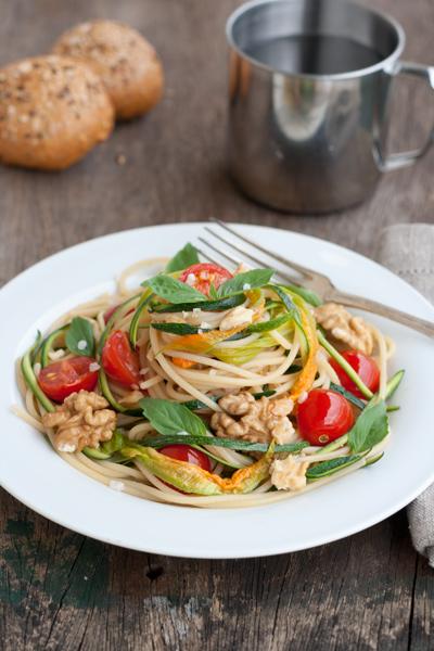 Pasta con zucchine crude, fiori, pomodori e noci